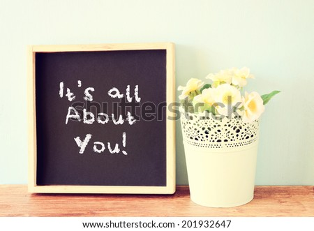 blackboard with the phrase it's all about you written on it. over wooden shelf and flowers.   - stock photo