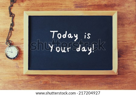 blackboard with the phrase today is your day written on it next to old clock over wooden table - stock photo
