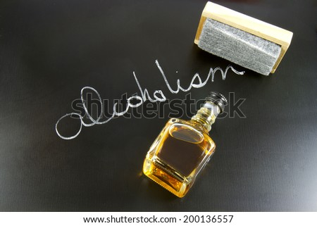 Blackboard with the word ALCOHOLISM written in chalk with an eraser and a mini bottle of whiskey - stock photo
