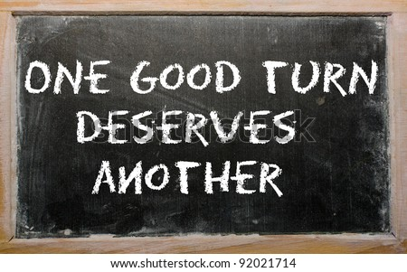 "Blackboard writings ""One good turn deserves another"" - stock photo"