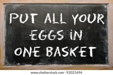 "Blackboard writings ""Put all your eggs in one basket"" - stock photo"