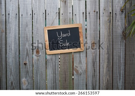 Blackboard yard sale sign on wooden fence - stock photo