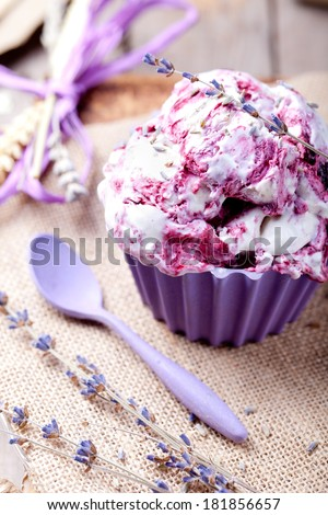 Blackcurrant and lavender ice cream with a lavender flower decoration in a ceramic bowl  on a textile and wooden background. Provence style. - stock photo
