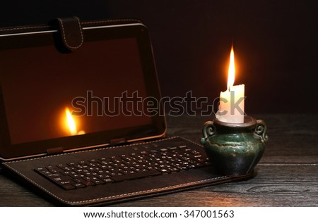 Blackout concept. Lighting candle near laptop with dark empty screen - stock photo
