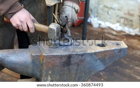 Blacksmith forges a horseshoe for horse - stock photo