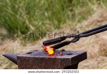 Blacksmith lays down a hot iron on anvil for forging in outdoor workshop - stock photo