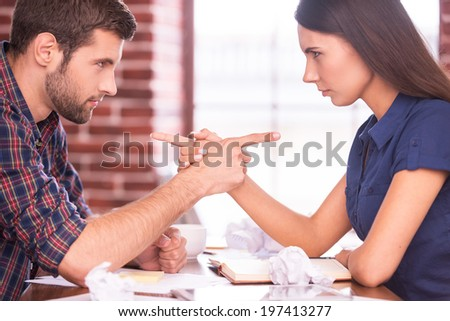 Blaming each other. Side view image of angry man and woman sitting face to face at the office table and pointing each other - stock photo