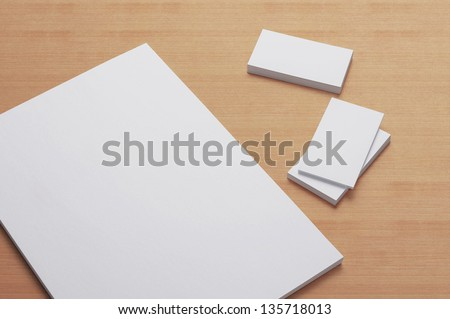 Blank A4 print paper and Business cards on wooden background / Stationary - stock photo