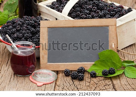 Blank advertising space on a slate blackboard in front of ripe blackberries and a jar blackberry jelly on a rustic wooden table - stock photo