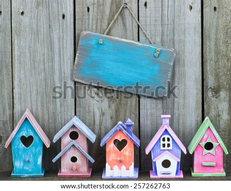 Blank aged wooden sign hanging over row of colorful pastel birdhouses with old weathered wood background - stock photo