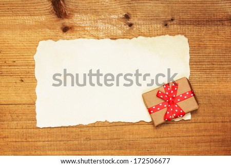 Blank and vintage gift box with ribbon bow on wooden background  - stock photo