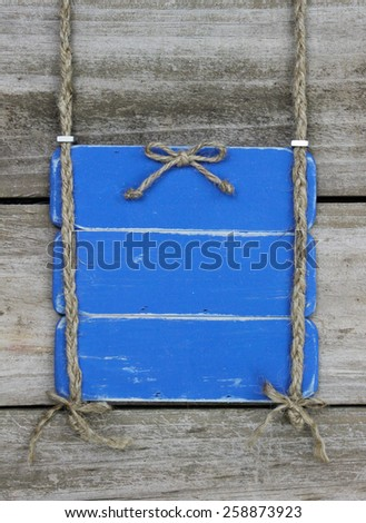 Blank antique blue sign with bow hanging by braided rope on rustic wood background - stock photo