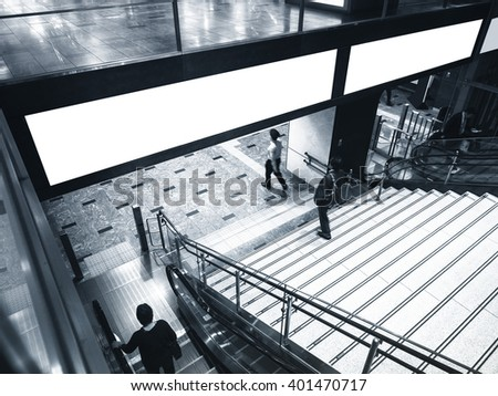 Blank Banner Billboard Media Display with Escalator Stairs and people in subway station - stock photo