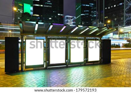 Blank billboard in city at night - stock photo