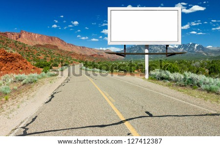 Blank billboard sign by empty highway through desert landscape - stock photo