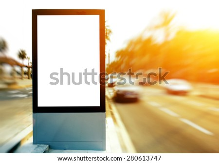 Blank billboard with copy space for your text message or content, outdoors advertising mock up, public information board on city road, flare sun light and motion blur effect with ride cars and taxi - stock photo