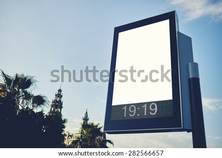 Blank billboard with copy space for your text message or content, public information board in the big town, advertising mock up empty banner in metropolitan city at beautiful sunny day, blur effect - stock photo