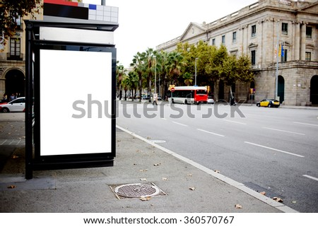 Blank billboard with copy space for your text message or promotional content, public information board in urban setting,bus stop Light box or advertising mock up with empty banner in metropolitan city - stock photo