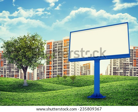 Blank billbord and tree against high-rise buildings over green hills with a few trees - stock photo