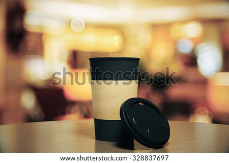 Blank black cup of coffee on a table at restaurant, mock up - stock photo