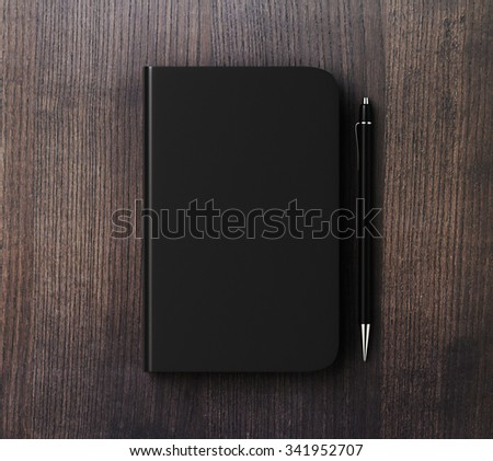 Blank black diary cover with pen on brown wooden table, mock up - stock photo