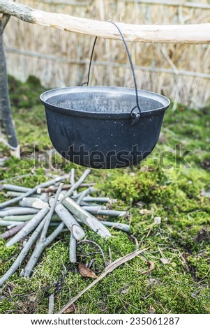 Blank black kettle hanging on makeshift wooden beam before cooking fire. - stock photo
