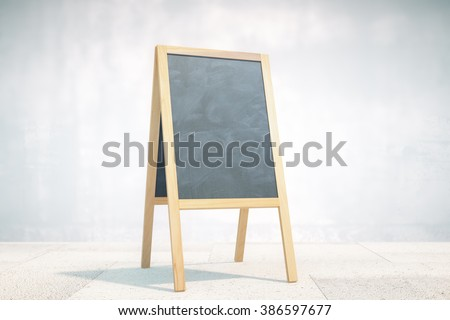 Blank black menu stand on concrete wall background. Mock up - stock photo