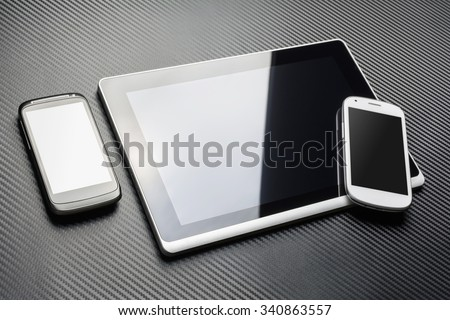 Blank Black Mobile Lying Next To A Business Tablet With Reflection And A White Smartphone On It's Corner, All Above A Carbon Layer - stock photo