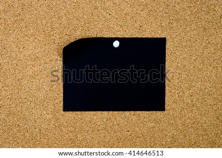 Blank black paper note pinned on cork board with white thumbtack, copy space available - stock photo