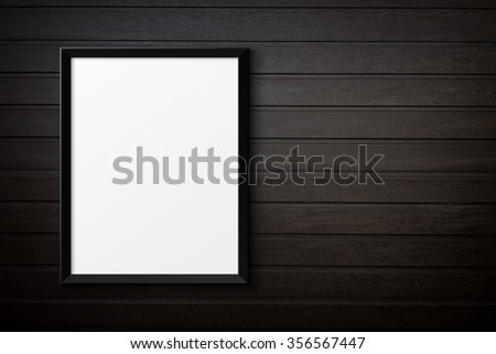 Blank black picture frame on the painted wood texture - stock photo