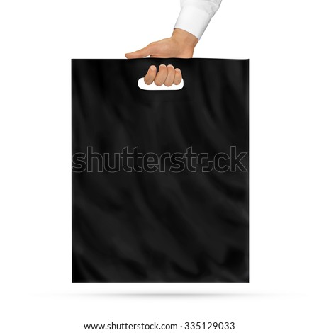 Blank black plastic bag mock up holding in hand. Empty polyethylene package mockup hold in hands isolated on white. Consumer pack ready for logo design or identity presentation. Product packet handle. - stock photo