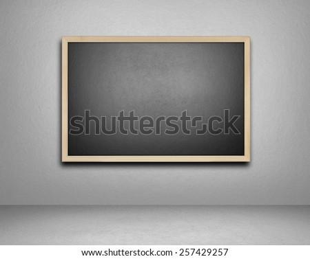 Blank blackboard on cement background - stock photo