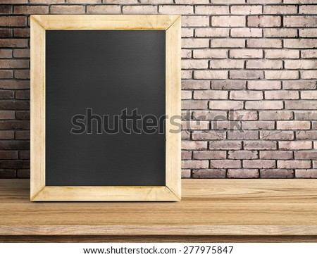 Blank blackboard on wooden table at red brick wall,Template mock up for adding your design and leave space beside frame for adding more text. - stock photo