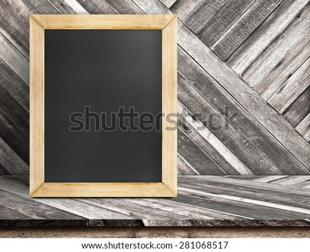 Blank blackboard wood frame on diagonal wooden table at diagonal wood wall,Template mock up for adding your design and leave space beside frame for adding more text - stock photo