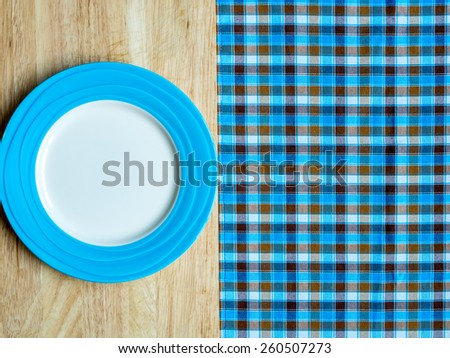 Blank blue plate on wooden table and checked tablecloth background - stock photo