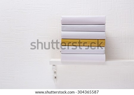 Blank books and yellow one on shelf on white wallpaper background - stock photo