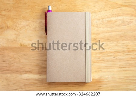 Blank brown notebook with pen on wood background - stock photo