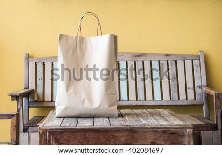 Blank brown paper bag on wooden. - stock photo