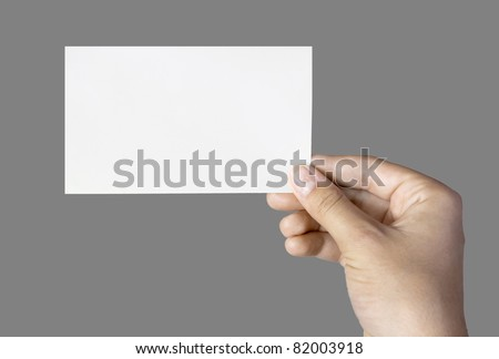 blank business card in a hand isolated on grey - stock photo
