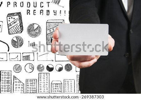 blank business card in hand businessman on background of the business plan - stock photo