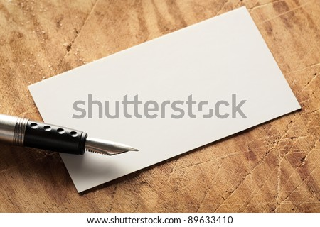 Blank business (visit) card on old wooden table with fountain pen. - stock photo