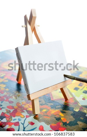 Blank canvas on easel on another picture frame with brush - stock photo