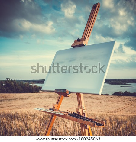 blank canvas rests on a easel on lake landscape, retro stylized - stock photo