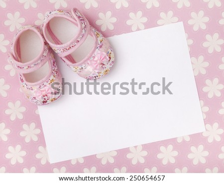 Blank card with baby girl shoes on a pastel pink floral background. - stock photo