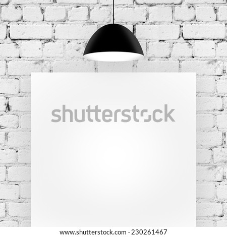 blank cardboard in brick room with ceiling lamp - stock photo