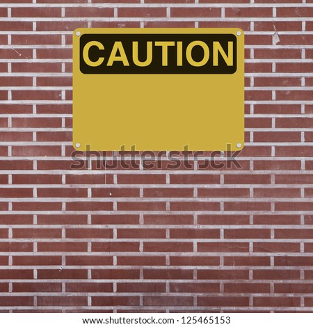 Blank caution sign mounted on a brick wall - stock photo