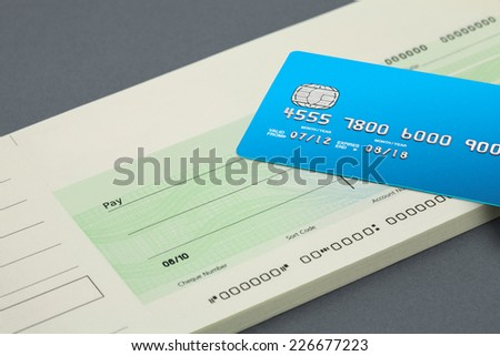 blank Cheque with a credit card on top - stock photo