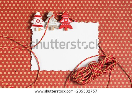 Blank christmas greeting card with holly berries and small decorative clothespins as firs - stock photo
