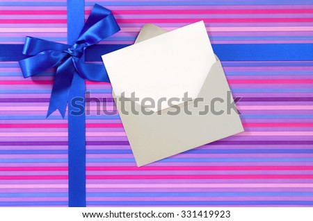 Blank Christmas or birthday card and envelope, blue gift ribbon bow on candy stripe wrapping paper, copy space - stock photo