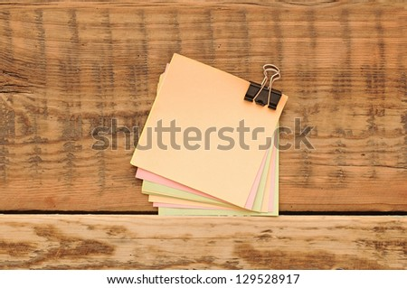 blank color stickers and paper clips on wooden table - stock photo